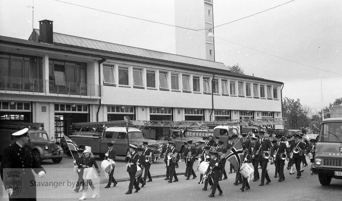 Brannmenn og korpset marsjerer av gårde fra brannstasjonen.