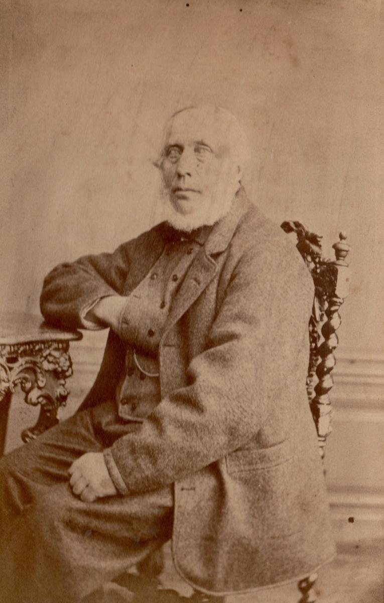 Portrett av eldre mann sittende på en stol ved et bord.