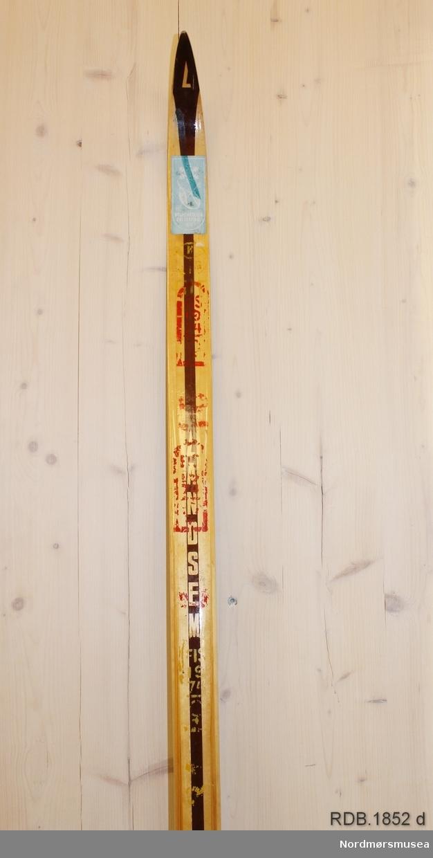 Tilnærmet jevnbred ski med svært liten bue. Bøy uten tupp. Tilspisset brett. Bakende litt oppbøyd. Rottefella hælstøtte med tagger. Rottefella binding. Dekorert med ei brun stripe på trehvit bunn.  Skiet har flere stempel etter skisesongen 1974.