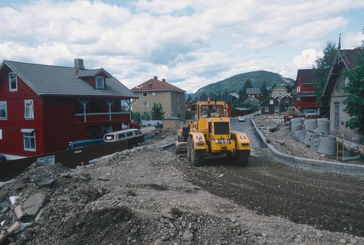 Lillehammer.  Nordsetervegen forbi Brannstasjonen under anlegg (Nordre tangent).  Brannstasjonen er det røde bygget til høyre.  Veghøvel.  Sett mot nord-vest.