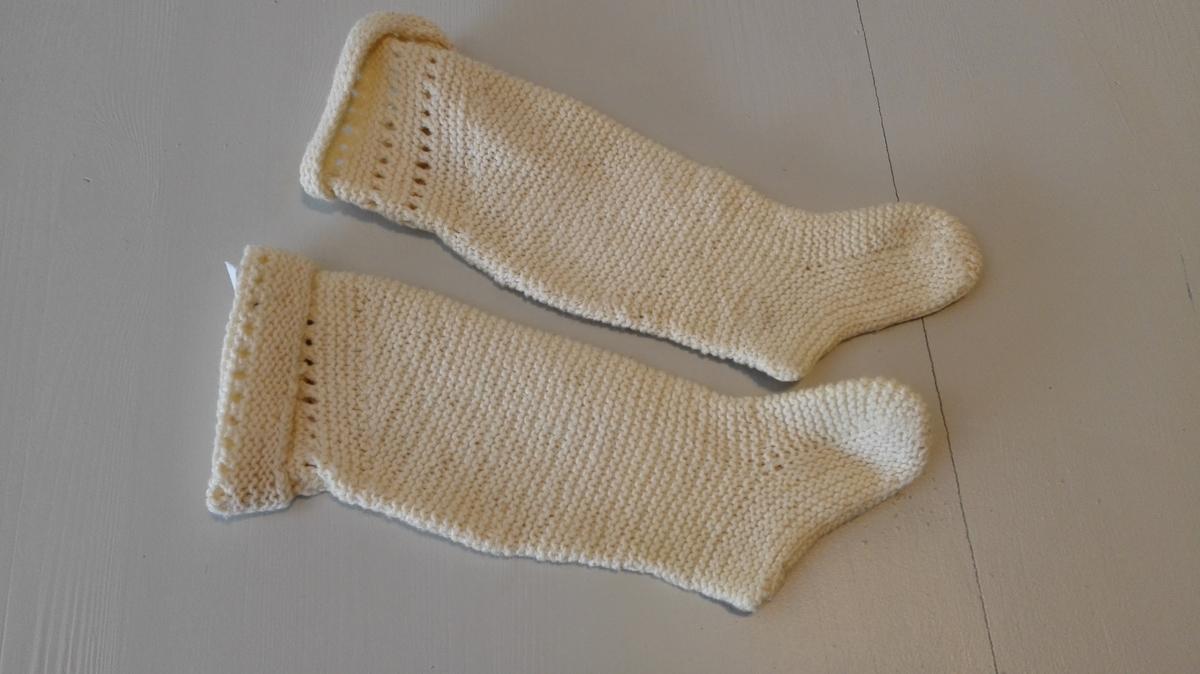 Strikka med tre holrender øvst i brotet. Felt i kalboti. Leggfelling. I sokken er vristpartiet strikka først. (hælemaskane står att) Så er det teke opp maskar langs vristparti, tå og hæl og strikka sålen på langs. Felling under heile foten.