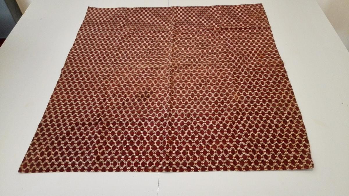 1 tørklæde.  1 tørklæde av trykmønstret brunt og hvidt lintøi, størrelse 80 x 72 cm.  Kjøpt paa auktion paa Storaker ved lensm. A. Faleide.