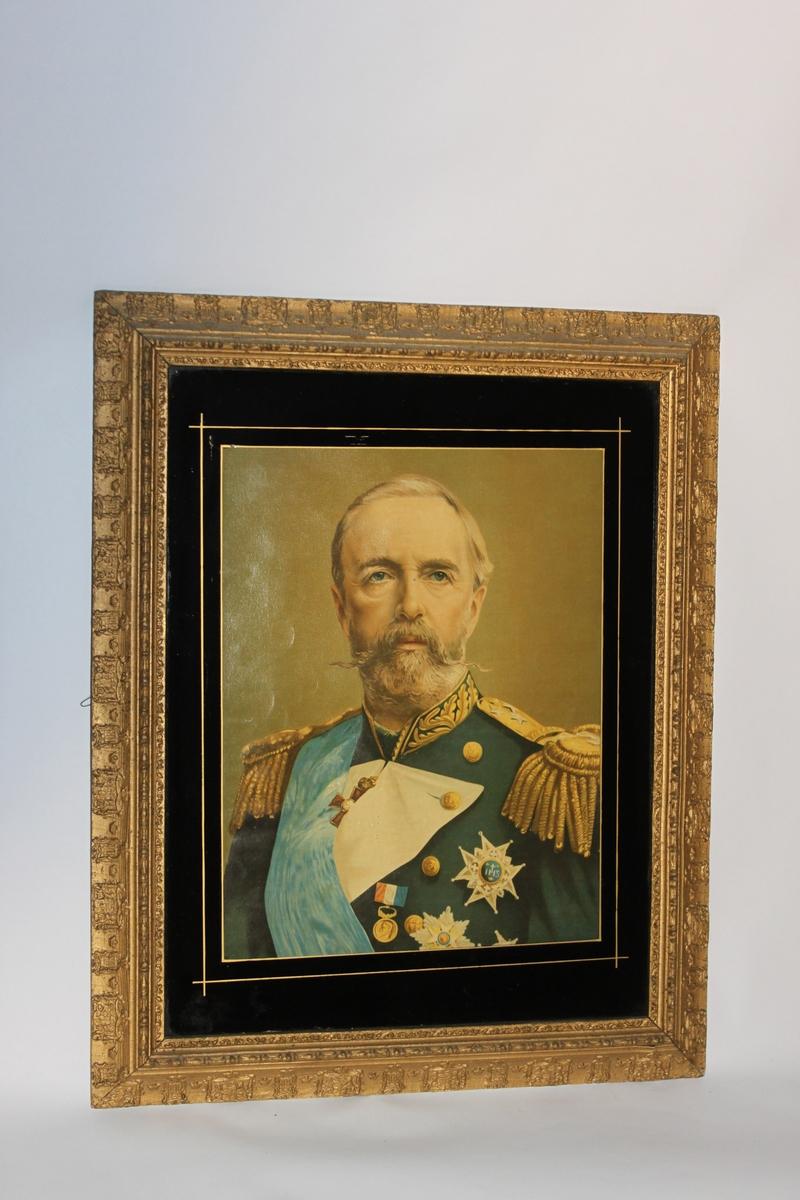 Oljetryck, litografiskt tryck med fernissad yta. Inom glas och med förgylld ram och svart passepartout. Föreställande kung Oscar II (1829-1907) i uniform. Den förgyllda ramen har Sveriges vapen inpräglat med jämna mellanrum runt hela ramen.