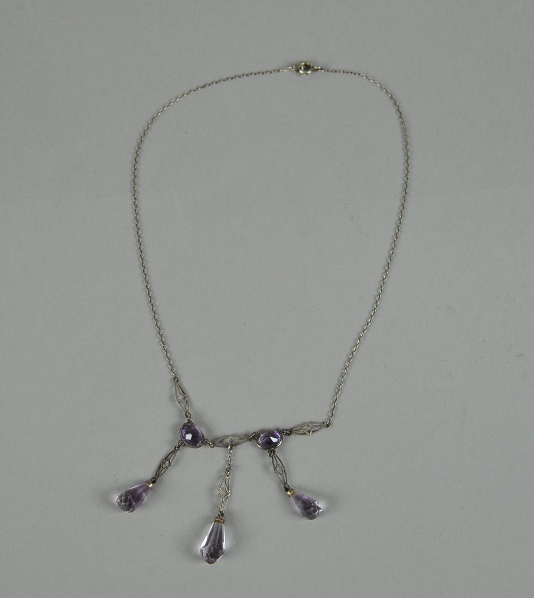 Halskjede av sølv. Kjedet har to ovale ametyster og tre dråpeformede ametyster, med dekorative mellomledd. Det er stempler på den ene hempen.