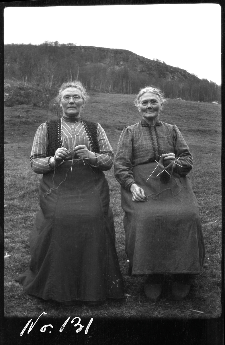 Portrett av to eldre damer som sitter og strikker utendørs.