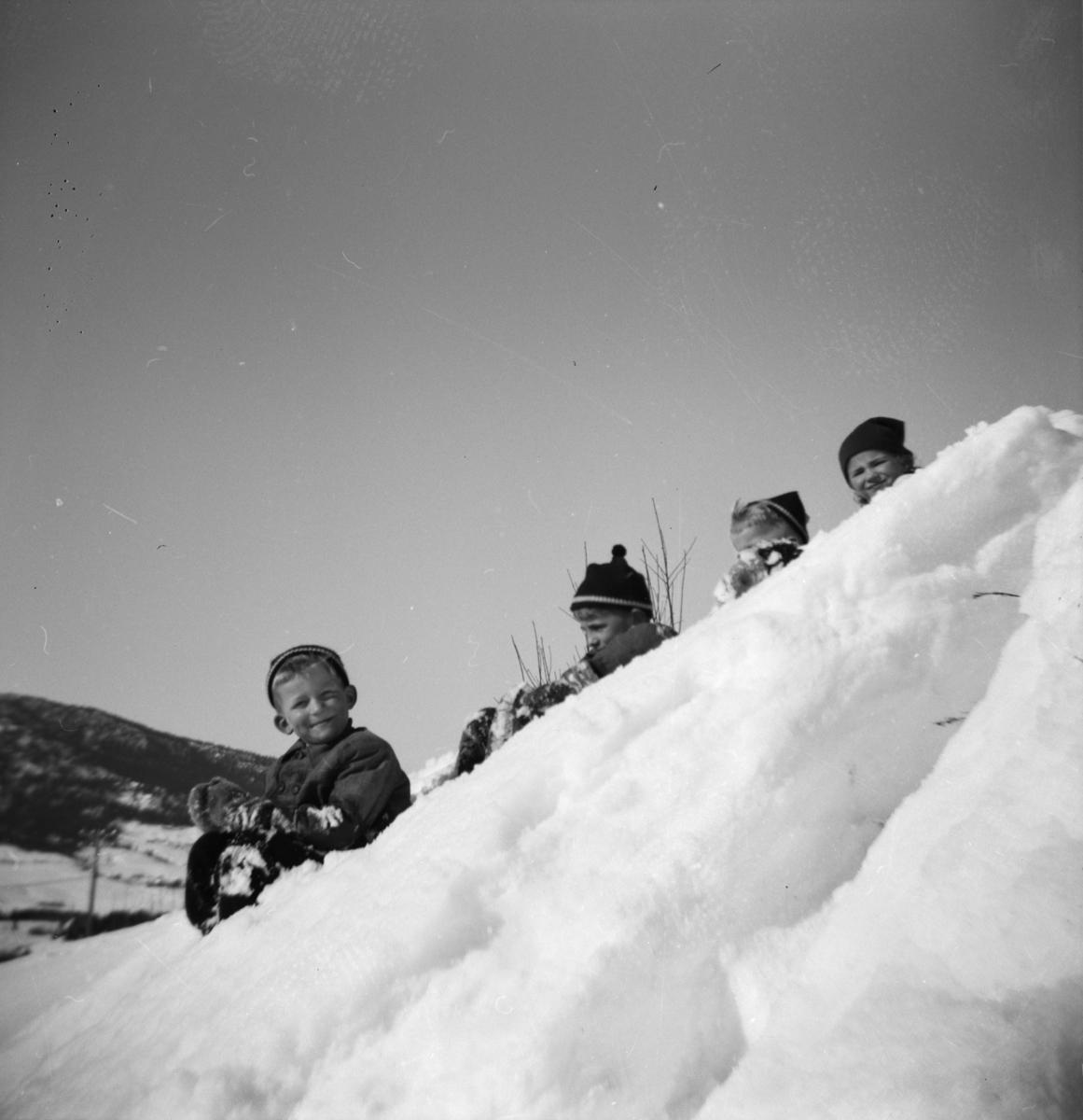 Fire barn som leker i snøen