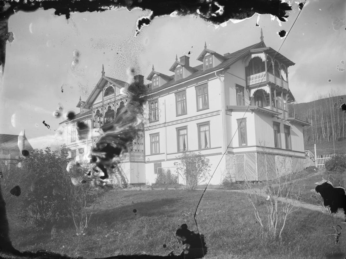 Vinstra Hotell fra baksiden, med karnappvinduer på  taket, utskårne verandaer og en av verandaene med glassmosaikk.