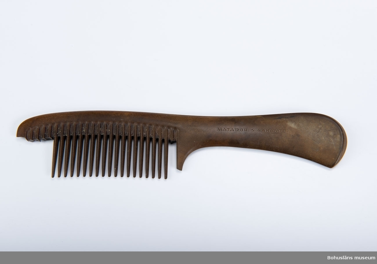 Brun plastkam med handtag.  Sex tänder avbrutna och saknas. Föremål från Brorssons Damfrisering i Kungshamn, se UM023941.