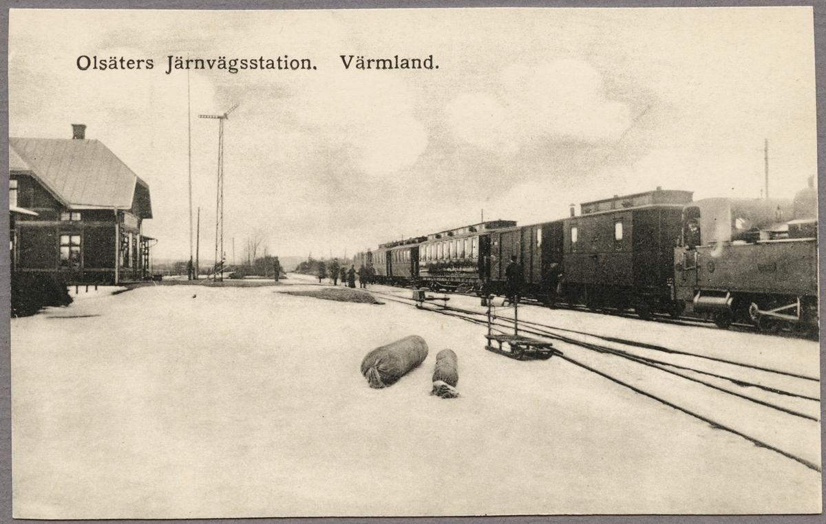 Stationsområde och tåg med vagnar under vintertid.
