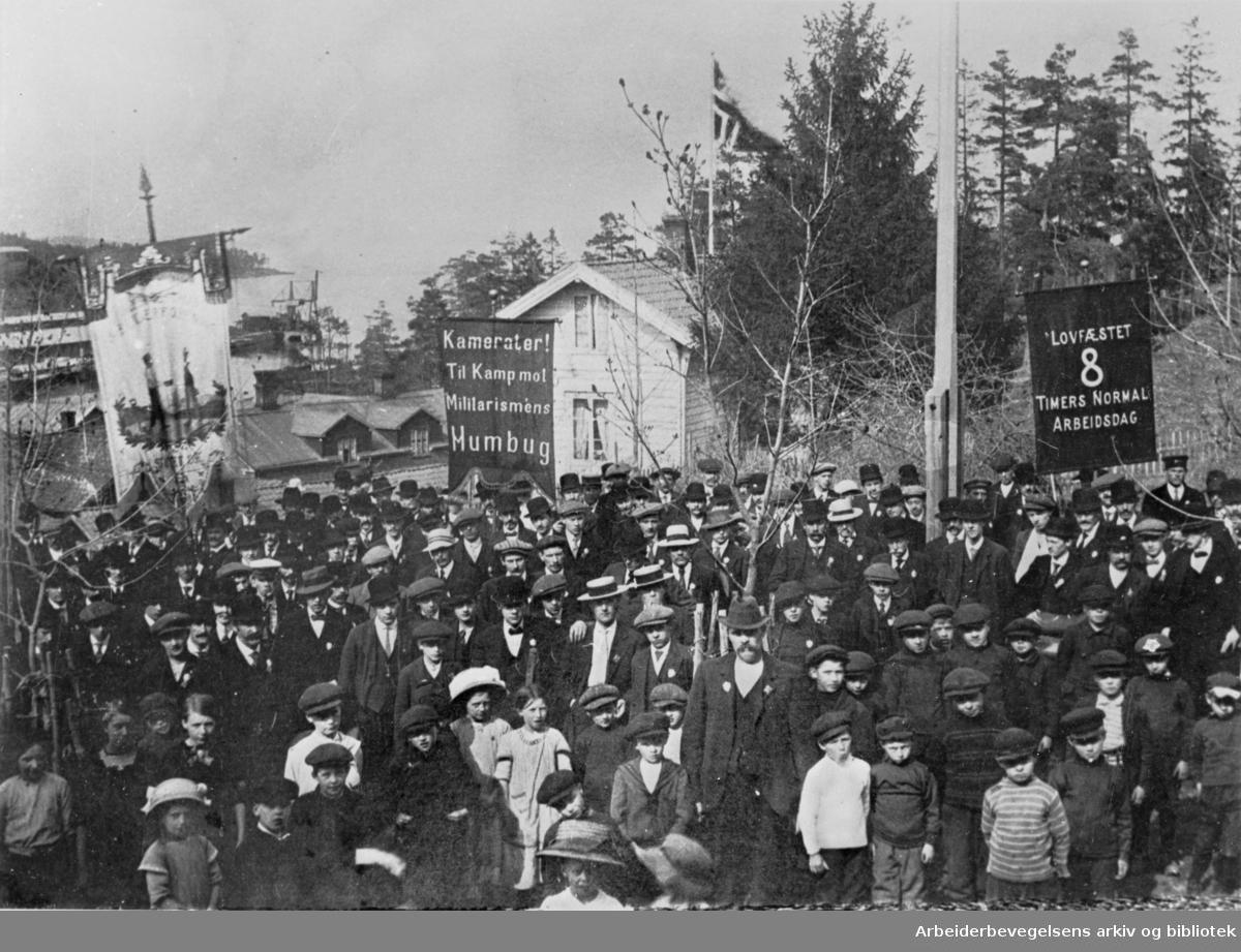 1. mai på Slemmestad i Røyken, 1909. Fanen til venstre tilhører Slemmestad Arbeiderforening. Paroler: Kamerater! Til Kamp mot Militarismens Humbug; Lovfæstet 8 timers normal arbeidsdag.