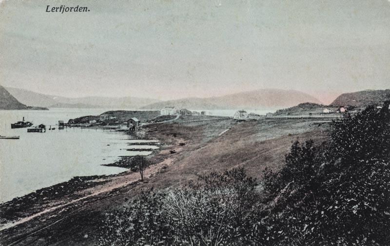 Leirfjord, Nedre-Leland. Oversiktsbilde av landskapet. Bildet er tatt mot Bergh-brygga (museum) med Breivika i bakgrunnen. Bildet er kolorert. Finnes også i s/hv som LEF.F.00086