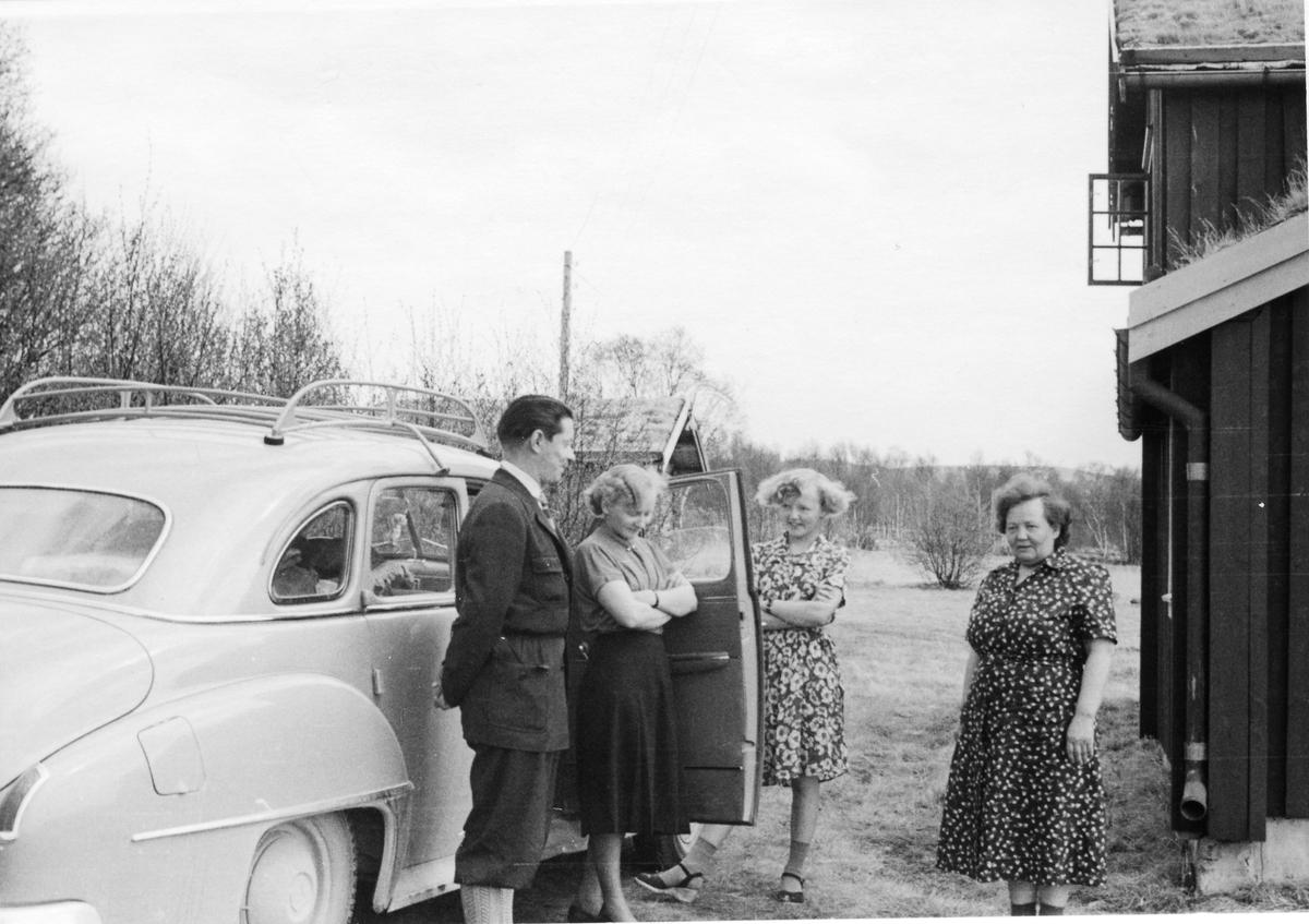 Tre damer og en mann ved bil på gårdsplass