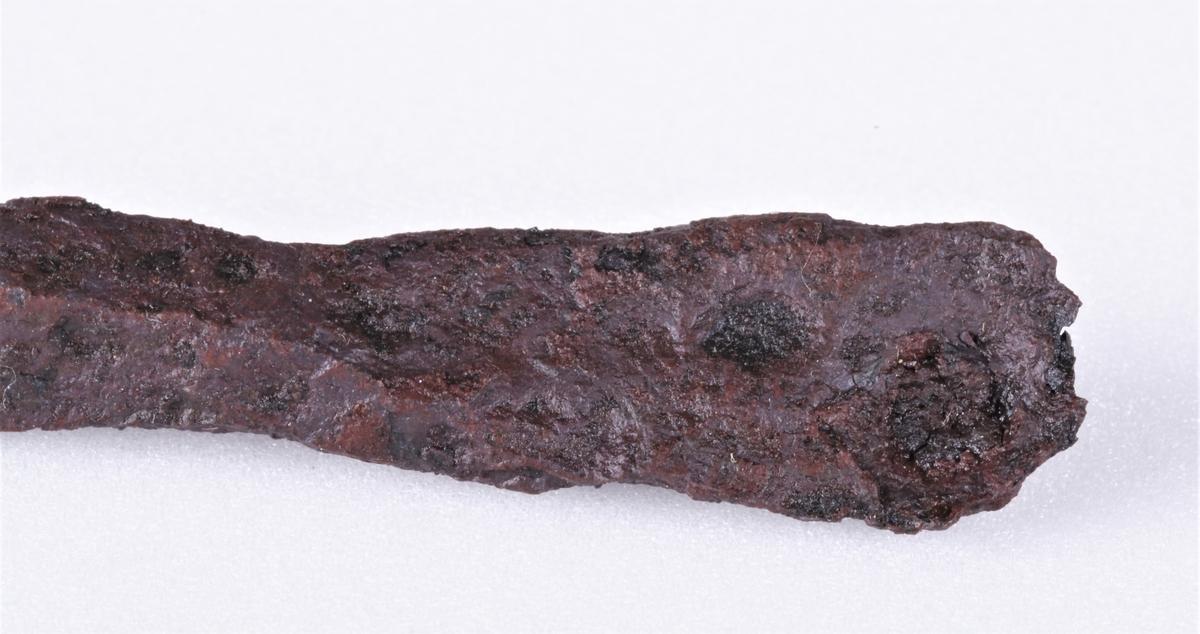 Jernbarre som type Rygh 438. Barren har form nærmest som ei langstrakt øks, med et rombeformlignende tverrsnitt i den smale enden. Nederst er det flatet ut som en egg. I den smale enden ser det ut til at det er forsøkt å lage et hull, men at det ikke har gått helt gjennom.