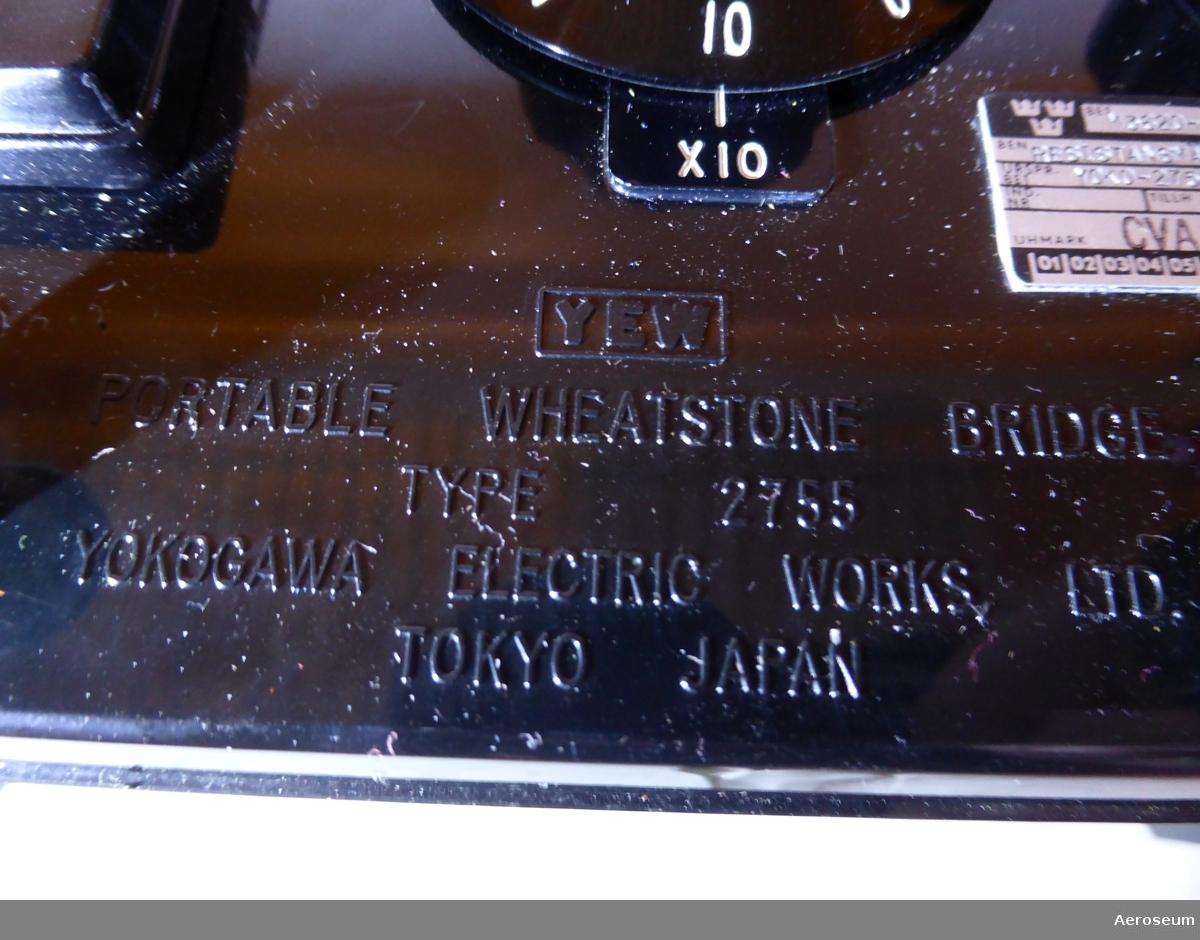 En orange televäska med en svart resistansbrygga i bakelit och en mätspänningskälla i grå metall. Tillverkade av Yokogawa Electric Works, Ltd. från Japan.