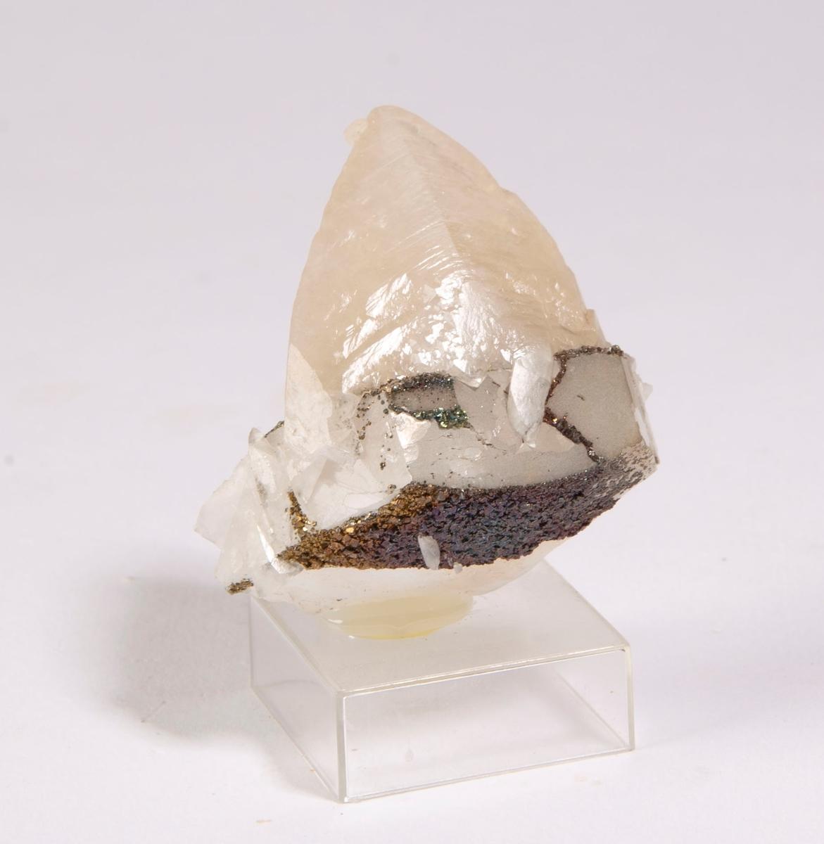 """""""Dog-tooth"""" krystall av kalsitt (3 cm lang) som påvekst på fragment av diskosformet krystall av kalsitt. Den tidligste generasjonen av kalsitt ble overvokst av pyritt før veksten av den seneste generasjonen av kalsitt. Mildigkeit Gottes gruve, 84 m."""