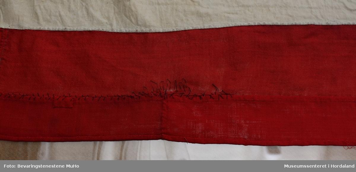 Stort flagg brukt i Mjeldalen, Osterøy. Flagget er sydd saman med handsaum av tre lengder naturfarga, tynt bomullsstoff. Det er kanta med raudt ullstoff. Flagget har påmalt dekor: Bokstavane MJELDALEN omringa av ein bladkrans med sløyfe nederst. Oppe i venstre hjørne er det norske flagget. Venstre sida er forsterka med linstoff der hampatau er tredd i til oppheng. Messingring oppe til venstre. Alt er handsauma, men med maskinsaumar der nokre nye delar raudt stoff er lappa inn.