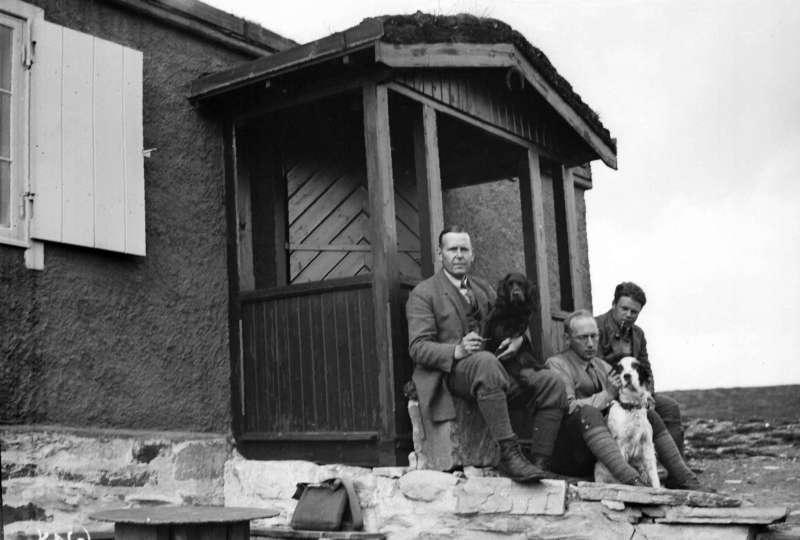 Ringebu. Flaksjøen. Jegere, tre menn med to hunder, foran Nils Anderssons hytte.