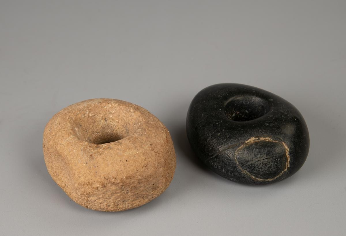a)Sort, basaltlignende sten. Oval sten med et gjennomgående rundt hull på midten med merker inni etter skaft eller materiale som har festet skaftet.  På den ene kortenden et rundt skall som er  limt på, har vært avslått.    b)Lyssvakt gyllenbrun sten som ligner sandsten. Oval formet  sten med over og underside svakt skrå. Gjennomgående hull på midten der åpningen vider seg ut til begge sider. Midt på hver langside en fordypning.