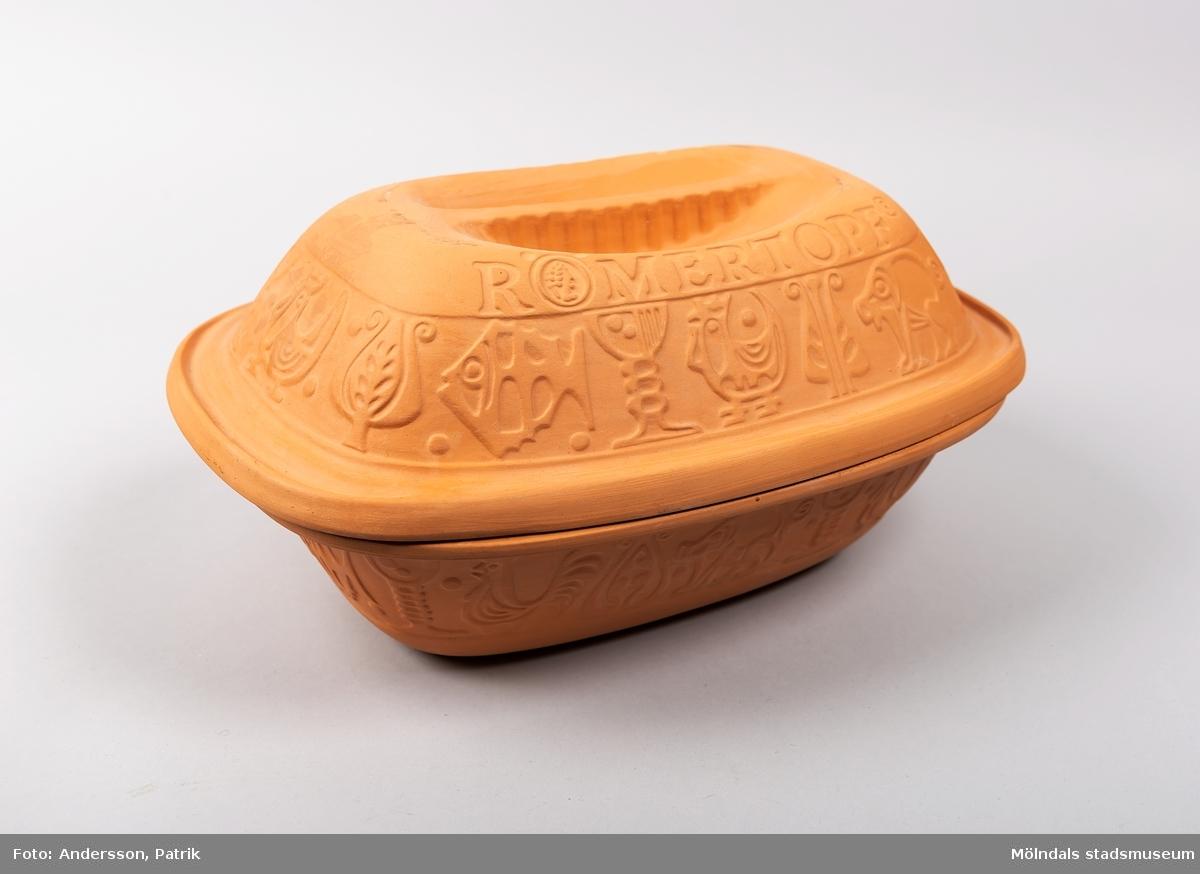 """Kokkärl för matlagning i ugn. Grytan är avlång oval till formen och tillverkad i ljusbrun lera. Den är dekorerad med en bård av bland annat tuppar.   Lergrytan """"Römertopf"""" som är tillverkad i Tyskland, blev mycket populär i Sverige under 1970-talet.   Lergrytan ska blötläggs i cirka 15 minuter, innan den kan användas för matlagning. Det går bra att tillaga kött, fisk, grönsaker och bröd i grytan. Grytan ställs in i kall ugn som sedan värms upp till önskad temperatur."""