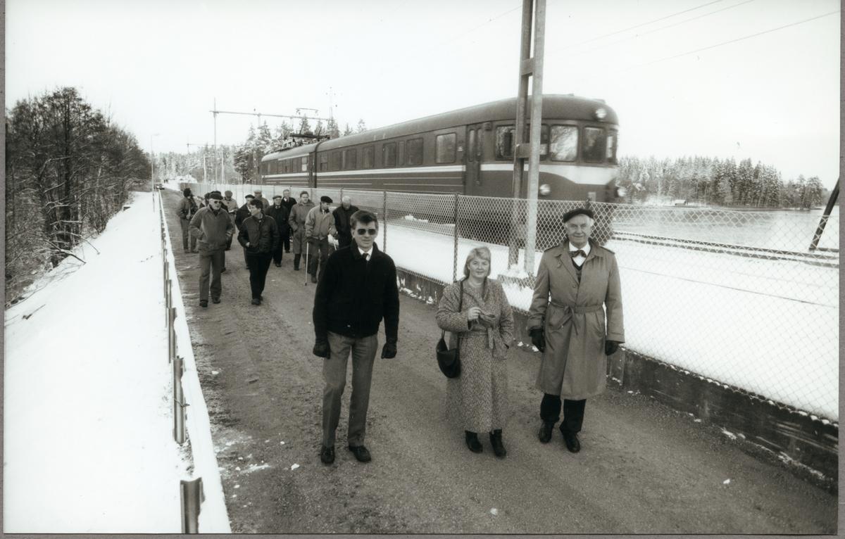 Representanter från kommunen och Trafikaktiebolaget Grängesberg - Oxelösunds Järnvägar, TGOJ går, den 1 december 1987 på den nya vägen som byggts vid Skölkärr och bort mot Bälgvikens stationshus, från vänster: Bo Aldurén, Nina Jarlbäck och Stig Nilsson.