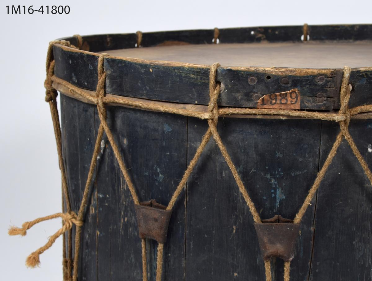 Bastrumma, blå-svart, med Skara vapen målat på sidan: Domkyrkan med stympade torn inom mantel. En etikett för SKVJ ilgods från Lundsbrunn samt en etikett med siffrorna 1989 är fastklistrade på trumman.