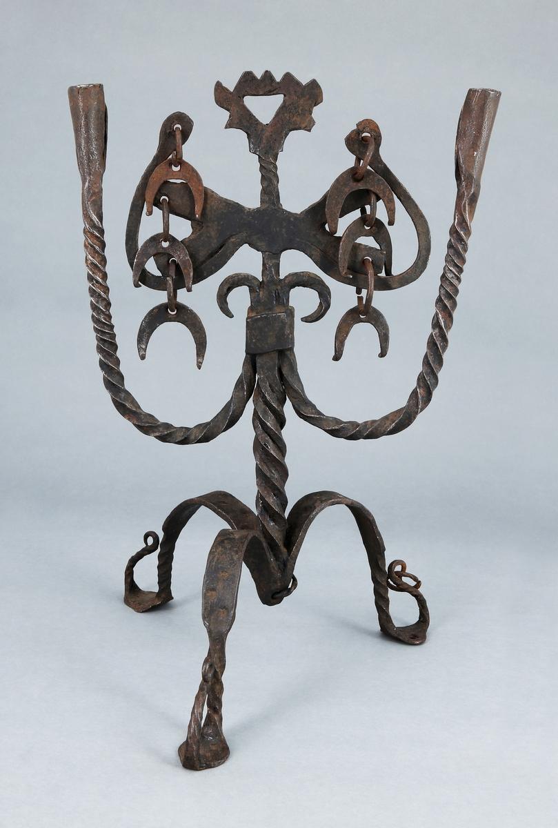 Ljusstake med spiralvriden stam som avslutas med  svängda ornament som på vardera sidan är prydda med tre ringar från vilka det hänger halvmånformade hängen. Från stammen utgår två spiralvridna armar som avslutas vardera med ljuspipa. Tre böjda ben med stämplad dekor och delvis spriralvridna. Benen med krokliknande avslutning. I en av dem hänger en ring.