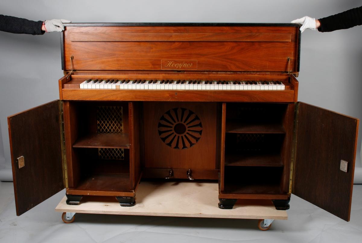 Omfang: AAA-a'''' (7 oktaver). Pianino innebygget i et skrivebord.  Finert skrivebord. To skap.  Fremre del av bordflate løtfes opp for å synliggjøre klaviaturet. Overdel løftes for å komme åt stemmestokk og stemmeskruer. To pedaler. Strenger monter på jernramme i x-form. To ekstra løse skapdører, ikke identifisert funksjon/plassering.