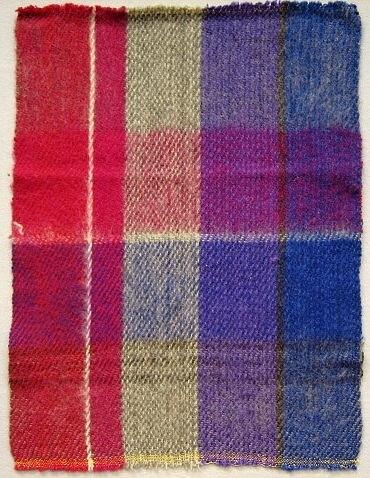Vävprov till rutig pläd vävd i kypertbindning.Varp: gotlandsgarn i rosa, blått, lila, vitt och gråttInslag: grått gotlandsgarn Vävnota Inv.nr 1037:79