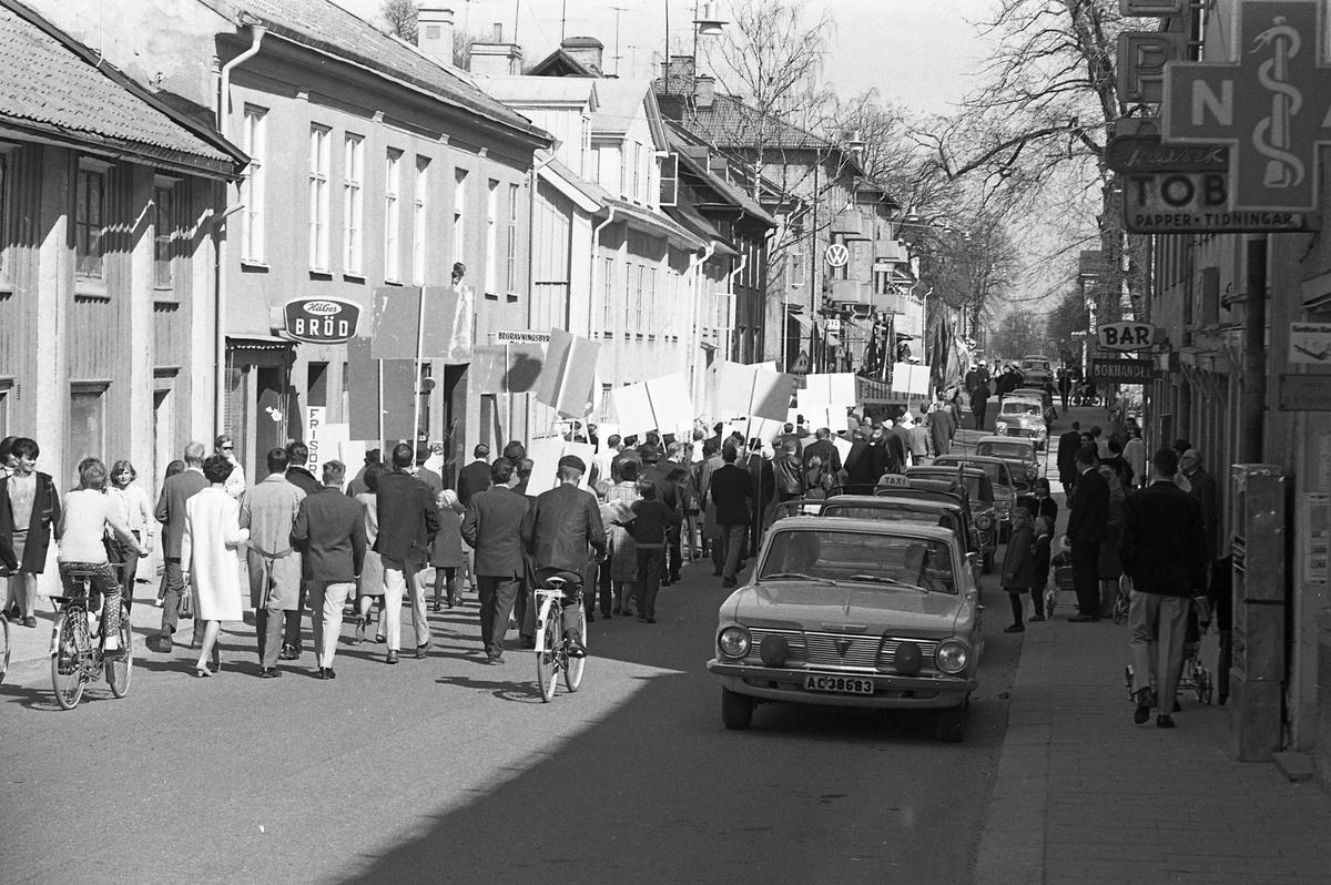 1:a majtåg. Demonstration på Nygatan, demonstranter med plakat. Personbilar och taxibil kör på vänster sida av gatan. Människor med cyklar och barnvagnar. Till vänster ligger HåGes Bröd och Frisören. Till höger ligger Apoteket, Tobaksaffären, en bar samt bokhandeln.