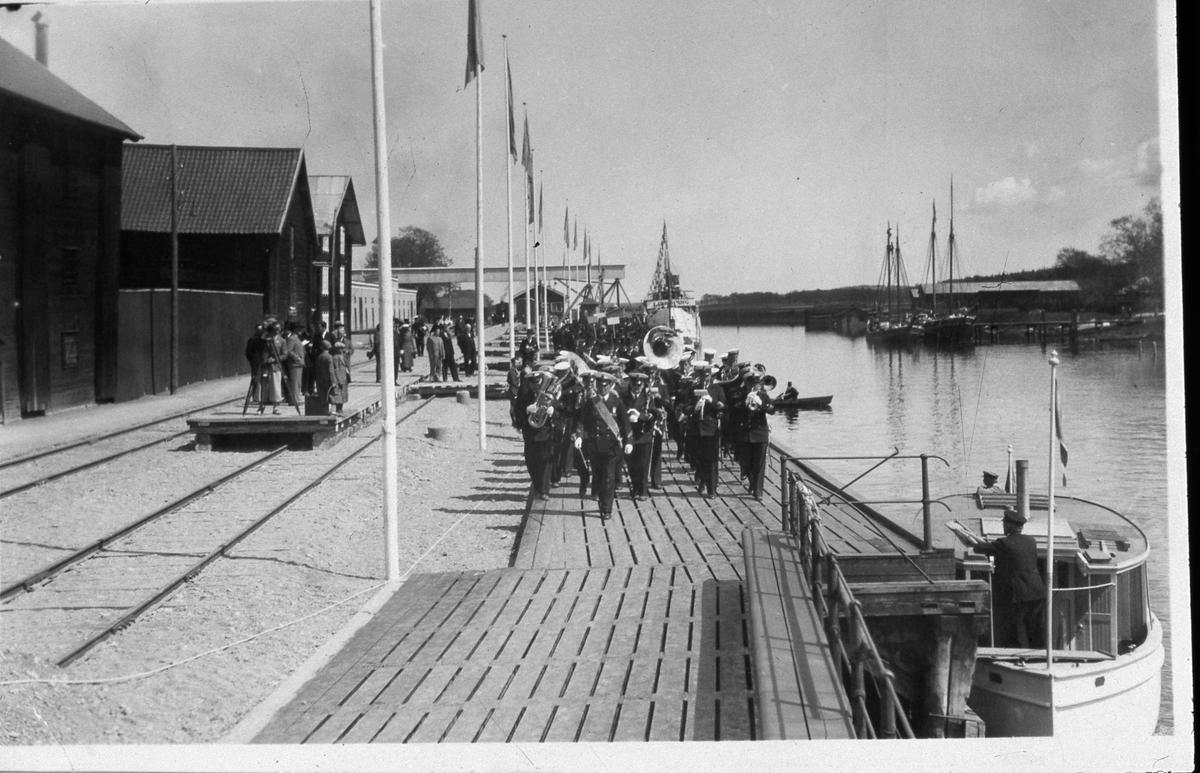 Här tågar Flottans Musikkår under ledning av Ivar Widner. De är vid hamnen och båtar ses i Arbogaån. Det långa horisontella röret hör till Centralföreningens silo. Publik och hamnmagasin till vänster. Flaggorna är hissade. Musikkåren är i Arboga för att delta i firandet av Sveriges Riksdags 500-årsjubileum. En stor publik samt stora delar av den kungliga familjen och höga politiker och tjänstemän kommer att närvara.