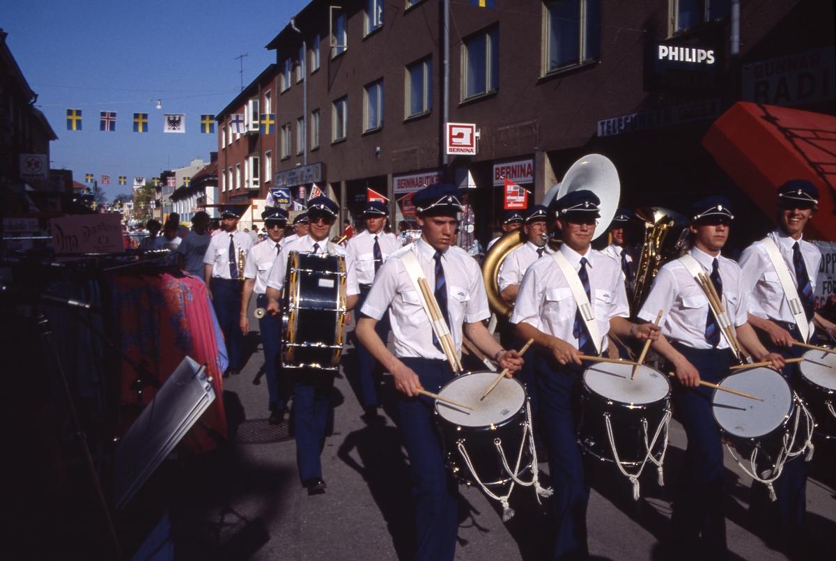 Arboga Blåsorkester marscherar på Nygatan under marknaden Arbogaträffen. Trumslagarna närmast i bild. Människor och marknadsstånd kantar vägen. Till vänster syns fotoaffären Expert. Till höger ligger Gunnar Karlssons Radio - TV och Berninabutiken.