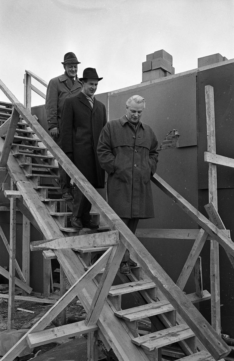 Arboga Bryggeri bygger egen bildverkstad med två portar. Tre män är på väg nerför en tillfällig trappa på en byggarbetsplats. Först går Karl Ivar Levert, han är chef för Arboga Bryggeri. Bakom honom går en oidentifierad man. Sist kommer bryggmästare Ture Anderberg.  Anläggningen var färdigbyggd 1899 och verksamheten startade 1 november samma år. 24 oktober 1980 tappades det sista ölet, på bryggeriet. Märket var Dart. Läs om Arboga Bryggeri i hembygdsföreningen Arboga Minnes årsbok 1981