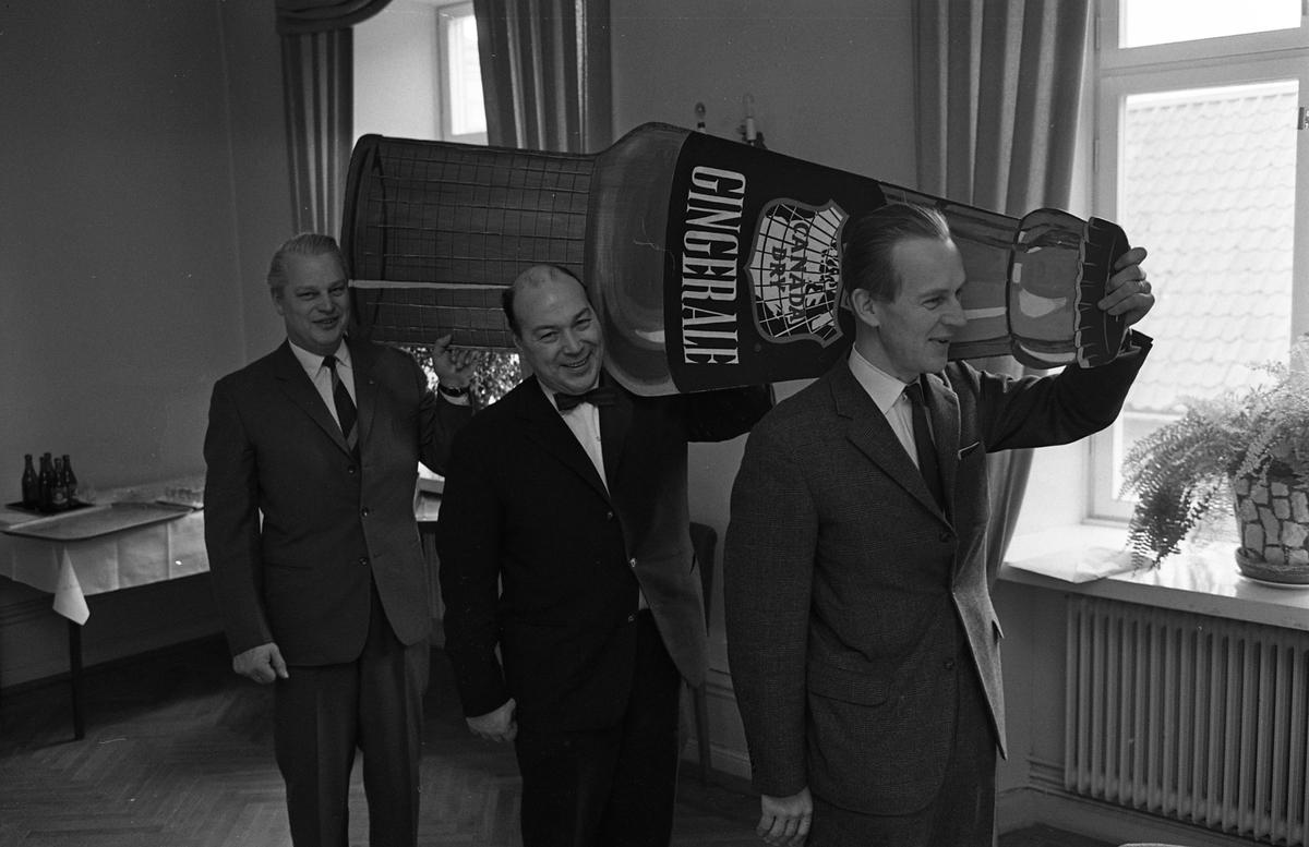 """Arboga Bryggeri introducerar, och pressvisar, Canada Dry. Tre kostymklädda män bär en stor pappmodell föreställande en ölflaska med kapsyl. Flaskan har texten """"Canada Dry Ginger Ale"""". De befinner sig i en lokal, någon våning upp. Ölflaskor står uppdukade på ett bord i bakgrunden. Längst bak går direktör Karl Ivar Levert (chef för bryggeriet), i mitten Torsten Adenby. Mannen i täten är okänd. Torsten är inbjuden i sin egenskap av kändis, han var manager bland annat för Gösta """"Snoddas"""" Nordgren.   Läs om Arboga Bryggeri i hembygdsföreningen Arboga Minnes årsbok 1981  Anläggningen var färdigbyggd 1899 och verksamheten startade 1 november samma år. 24 oktober 1980 tappades det sista ölet, på bryggeriet. Märket var Dart."""