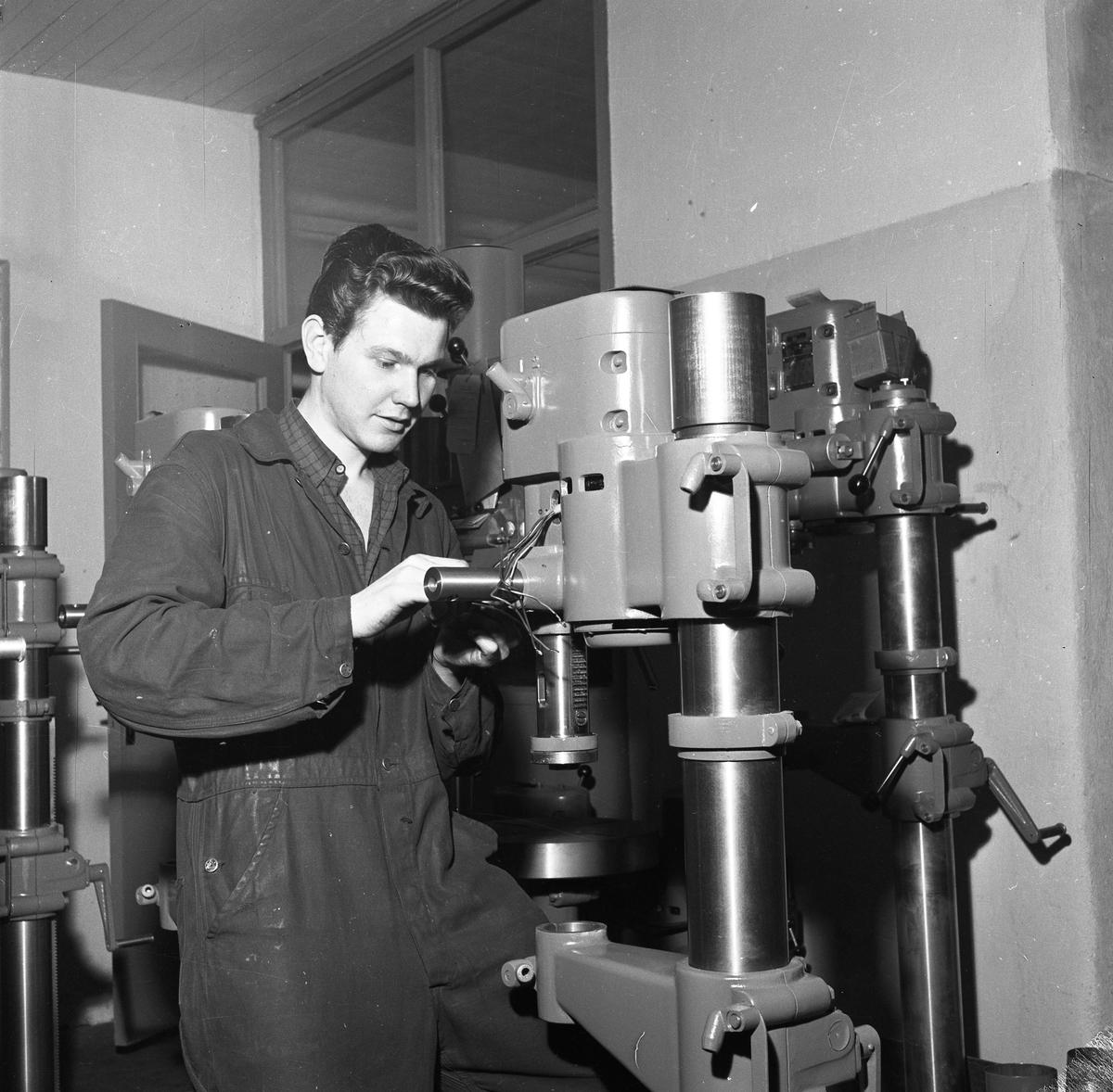 Arboga Maskiner, interiör. En man, iklädd overall, arbetar vid en pelarborrmaskin i en fabrikslokal.  Bilden tagen i samband med AB Arboga Maskiners 25-årsjubileum. Företaget startade 1934 och tillverkar borr-och slipmaskiner.  Läs, om företaget, i Reinhold Carlssons bok Arboga objektivt sett.