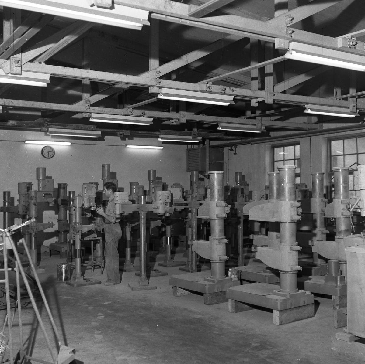 Arboga Maskiner, interiör. Ett fabriksrum är fullt av maskinpjäser. En man arbetar i lokalen. En klocka hänger på väggen. Bilden är tagen i samband med AB Arboga Maskiners 25-årsjubileum. Företaget startade 1934 och bygger borr- och slipmaskiner.  Läs mer, i Reinhold Carlssons bok Arboga objektivt sett.