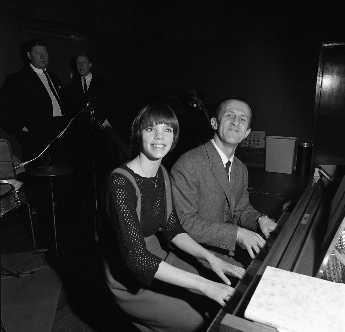 Arbogabor närvarar vid sändningen av Frukostklubben, ett underhållningsprogram som sänds på lördagsmorgnar. En kvinna och en man spelar fyrhändigt på pianot.