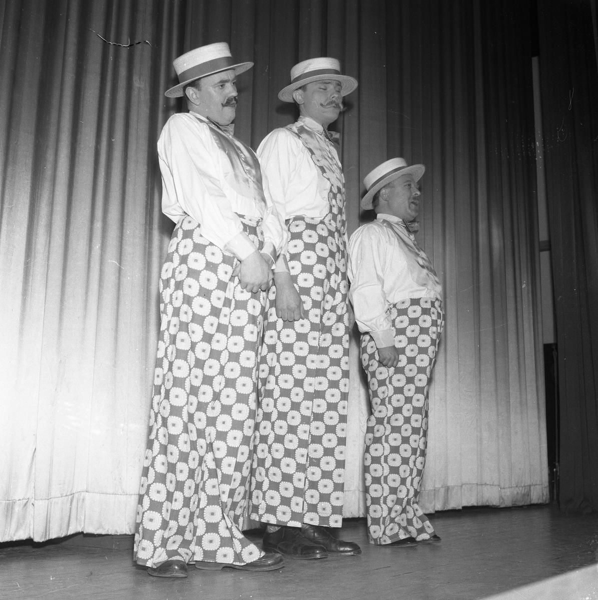 Deltagarna i Arbogarevyn spelar upp sin Jubileumsrevy. På scenen står tre herrar i samma sorts utstyrsel. Mannen längst till vänster kan vara Rune Ström.