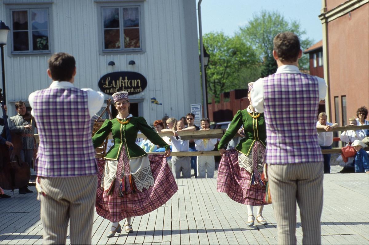 Arbogaträffen. Uppvisning av en utländs dansgrupp. I orkestern syns en fiol och en kontrabas. Uppvisningen sker på en uppbyggd dansbana på Stora torget. Publiken står nedanför och tittar på. I bakgrunden syns butik Lyktan och infarten till Västerlånggatan.