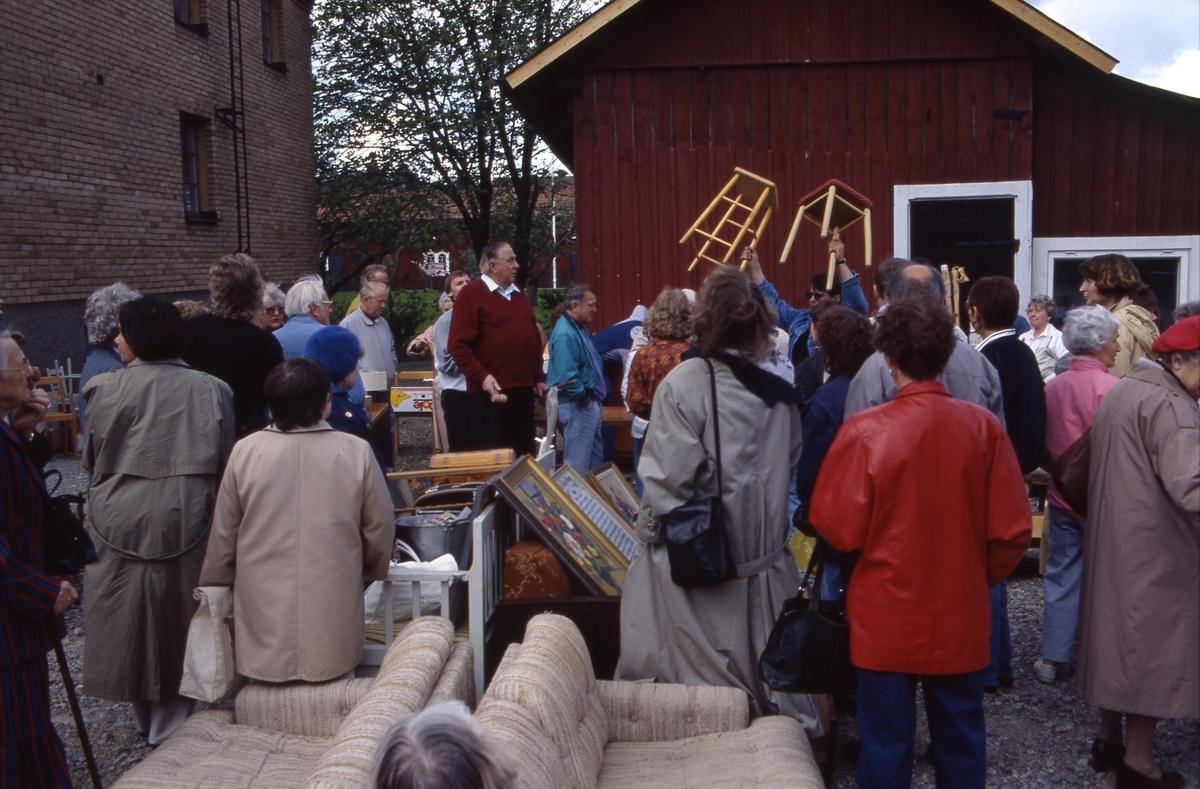 Auktion utomhus. Auktionsförrättaren står mitt i bilden med klubban i handen. Två pallar lyfts upp för budgivning. Människor rör sig i området. En soffgrupp står på grusplanen.