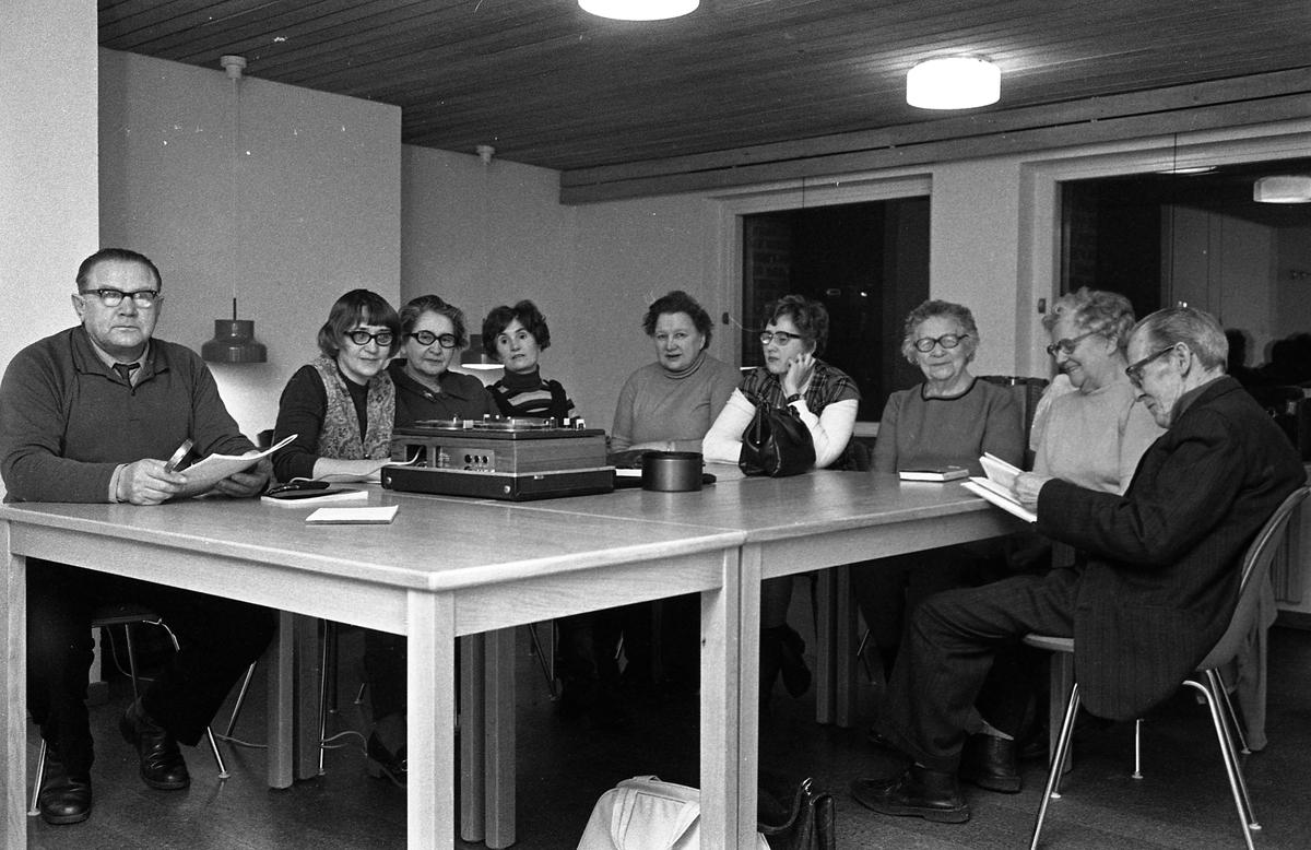 Gissningsvis en studiecirkel där mannen längst till vänster är kursledare. Nio personer, män och kvinnor, sitter runt bordet. På bordet står en rullbandspelare. Fru Lövgren (tredje personen från vänster) är här tillsammans med sina döttrar (andra och sjätte personen från vänster).  Platsen är ett studierum på biblioteket.