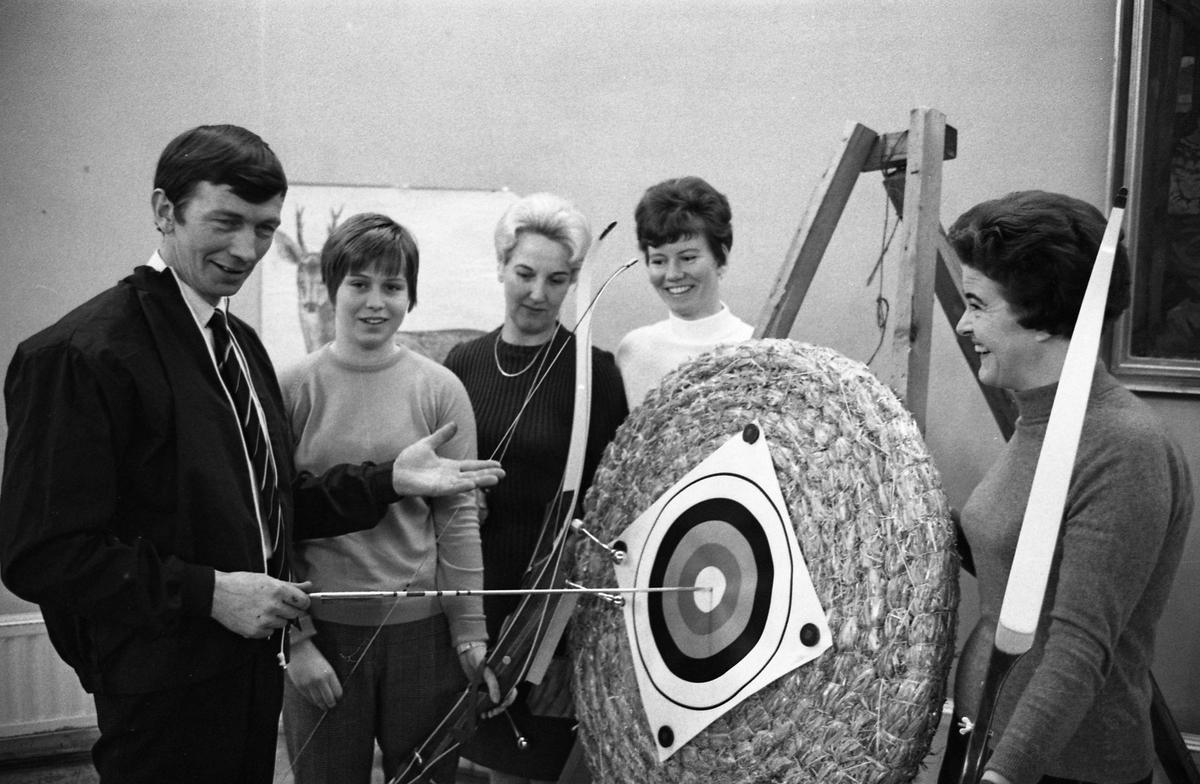 Bågskyttekurs. Fem personer runt en måltavla med en pil i mitten. Kvinnan i vit jumper är Kerttu Klotz