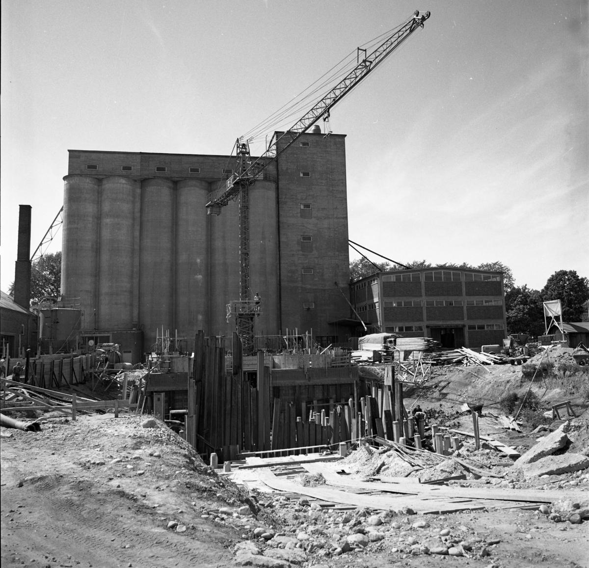 Centralföreningen bygger nytt. Lyftkran och bräder. Silon i bakgrunden.