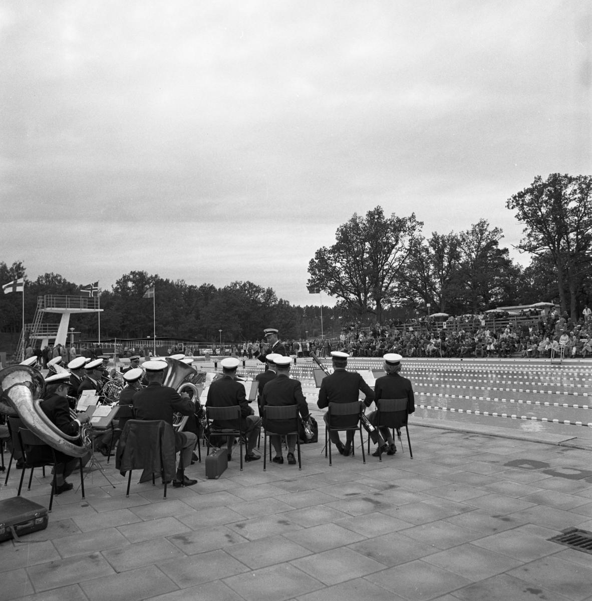 Musikkåren spelar vid invigningen av Ekbacksbadets utomhusbassäng! Publiken sitter på läktaren på andra sidan poolen. Hopptornet ses i bakgrunden.
