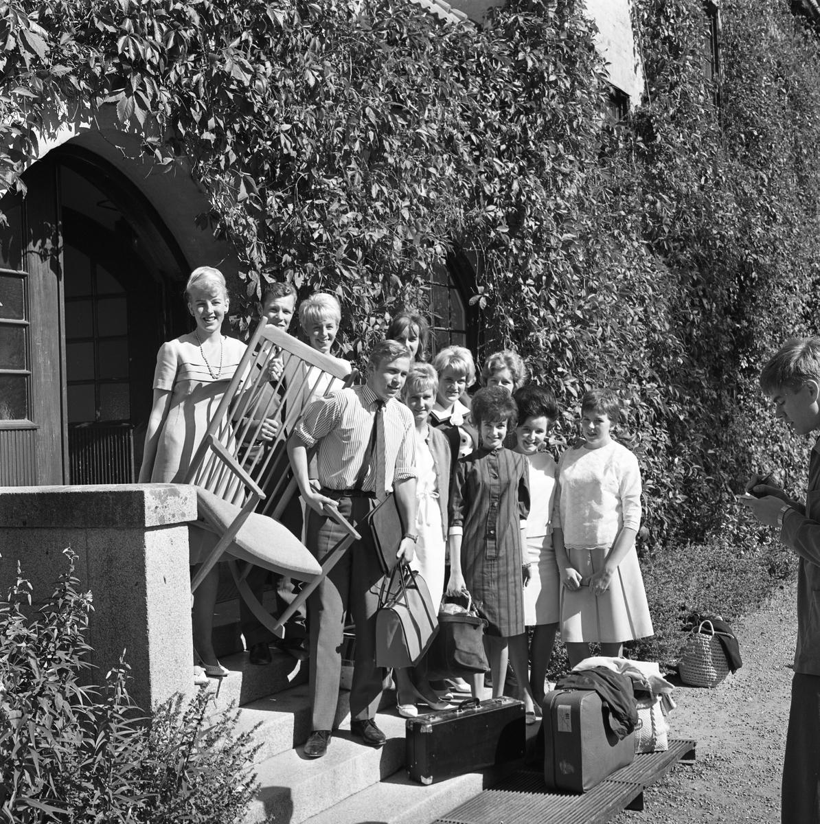 Elever vid Fellingsbro folkhögskola Nio unga kvinnor och två män står på en trappa utanför en port. Väggen är täckt av vildvin. De bär på en karmstol. Två resväskor och annat bagage står på grusgången. En man tittar i en anteckningsbok.