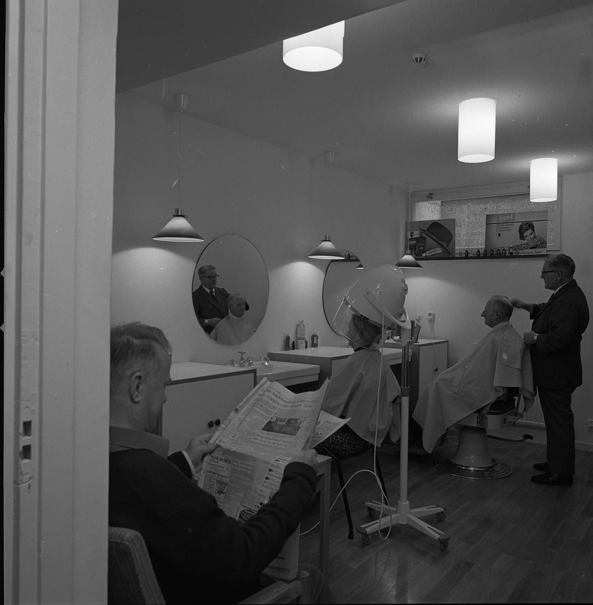 Frisör Axel Fritiof Strandberg (kallad Atschy) i salongen på det nyöppnade ålderdomshemmet Strömsborg. Axel klipper en kund. En kvinna sitter i torkhuven. En man läser en tidning.