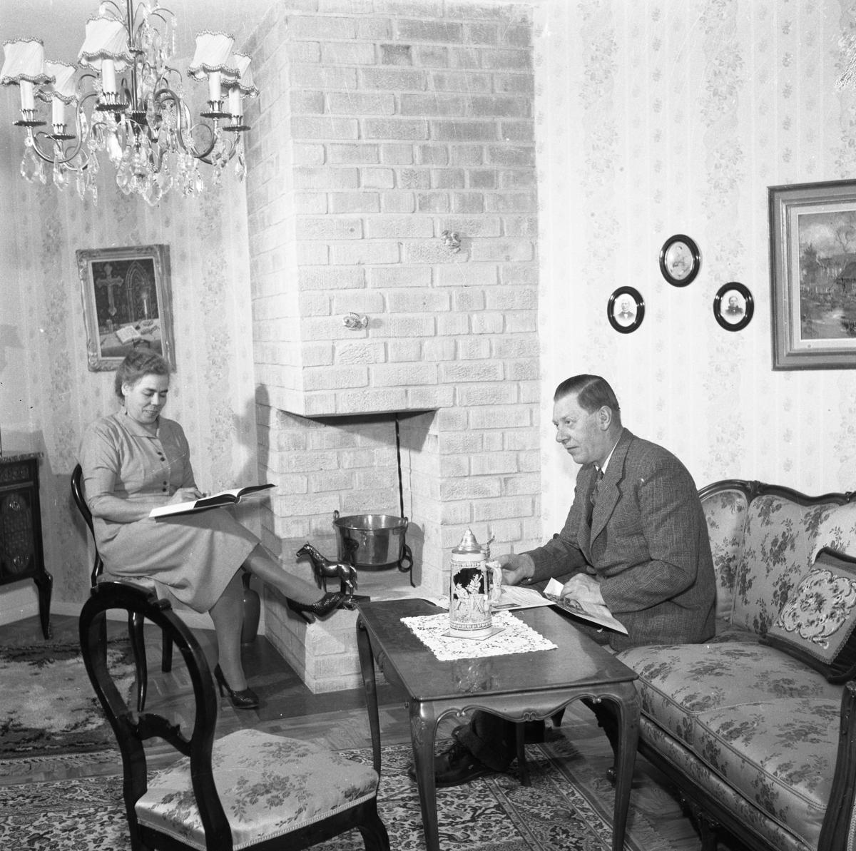 Färghandlare Valle Carlsson med hustru Maggie. Makarna sitter i vardagsrummet och läser. I hörnet finns en öppen spis. På bordet står en ölsejdel. Mannen sitter i soffan, hans fru sitter på en stol. Det hänger tavlor på väggarna. Interiör.