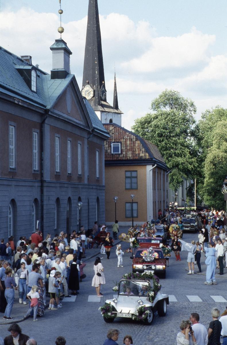 Arbogakarnevalen pågår. Här ses paraden ha nått Rådhusgatan. Bilar i kortege. Uppklädda dansgrupper. Publik på trottoaren. Till vänster ses rådhuset och i bakgrunden syns tornet på Heliga Trefaldighetskyrkan.