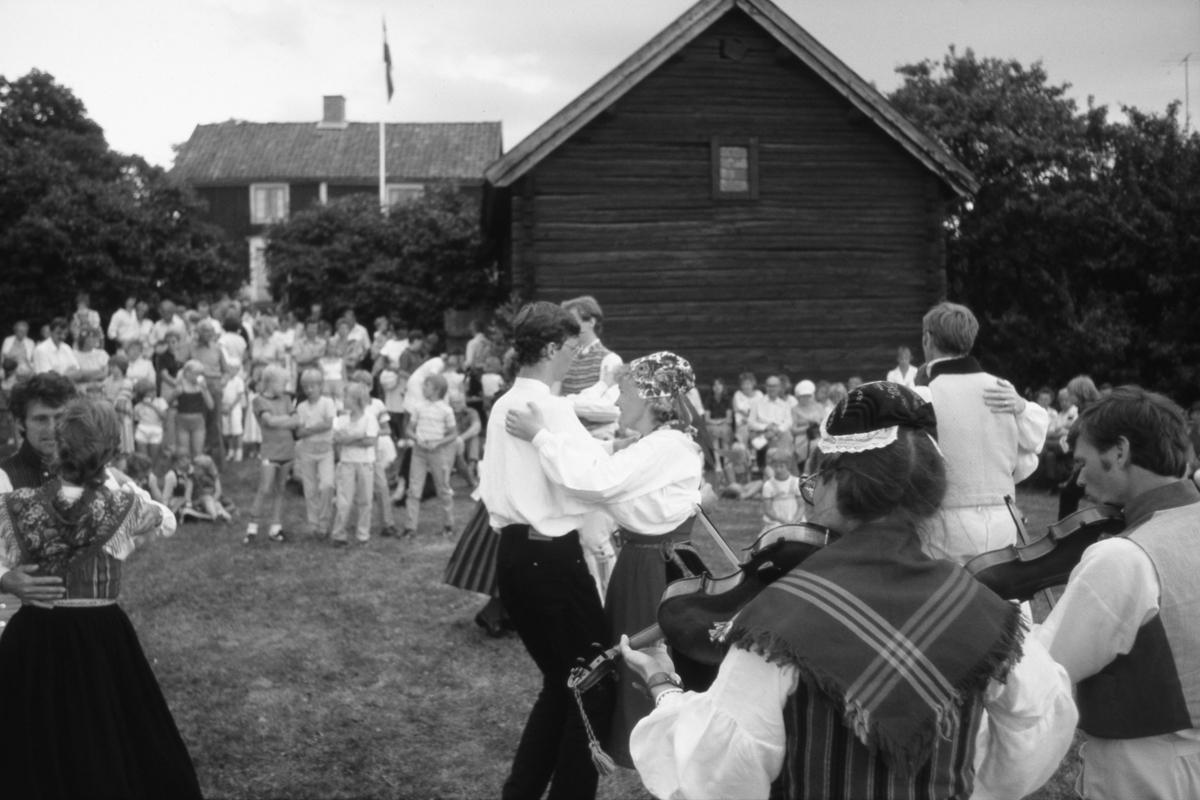 Midsommarfirande på hembygdsgården, Abramsgården, i Medåker. Arboga Folkdansgille uppträder för en stor publik. Till vänster dansar Karl-Berthold (Kalle) Widholm och Lilly Måård. Paret mitt i bild är Stefan Törnqvist och Kristina Olsson. Bilden är tagen 1982 eller 1983.