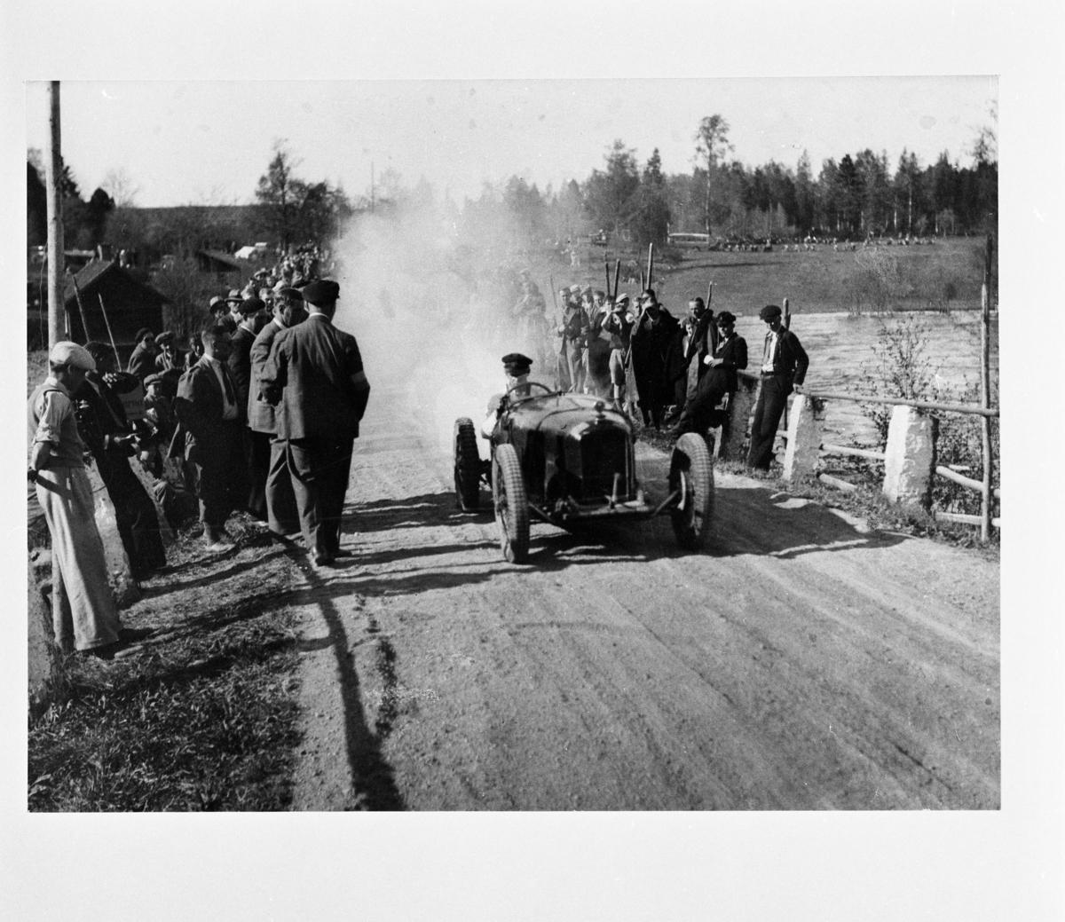 Reproduktion, Röfors. En man kör en bil/traktor med stort rökmoln bakom. Publiken står i vägkanten.