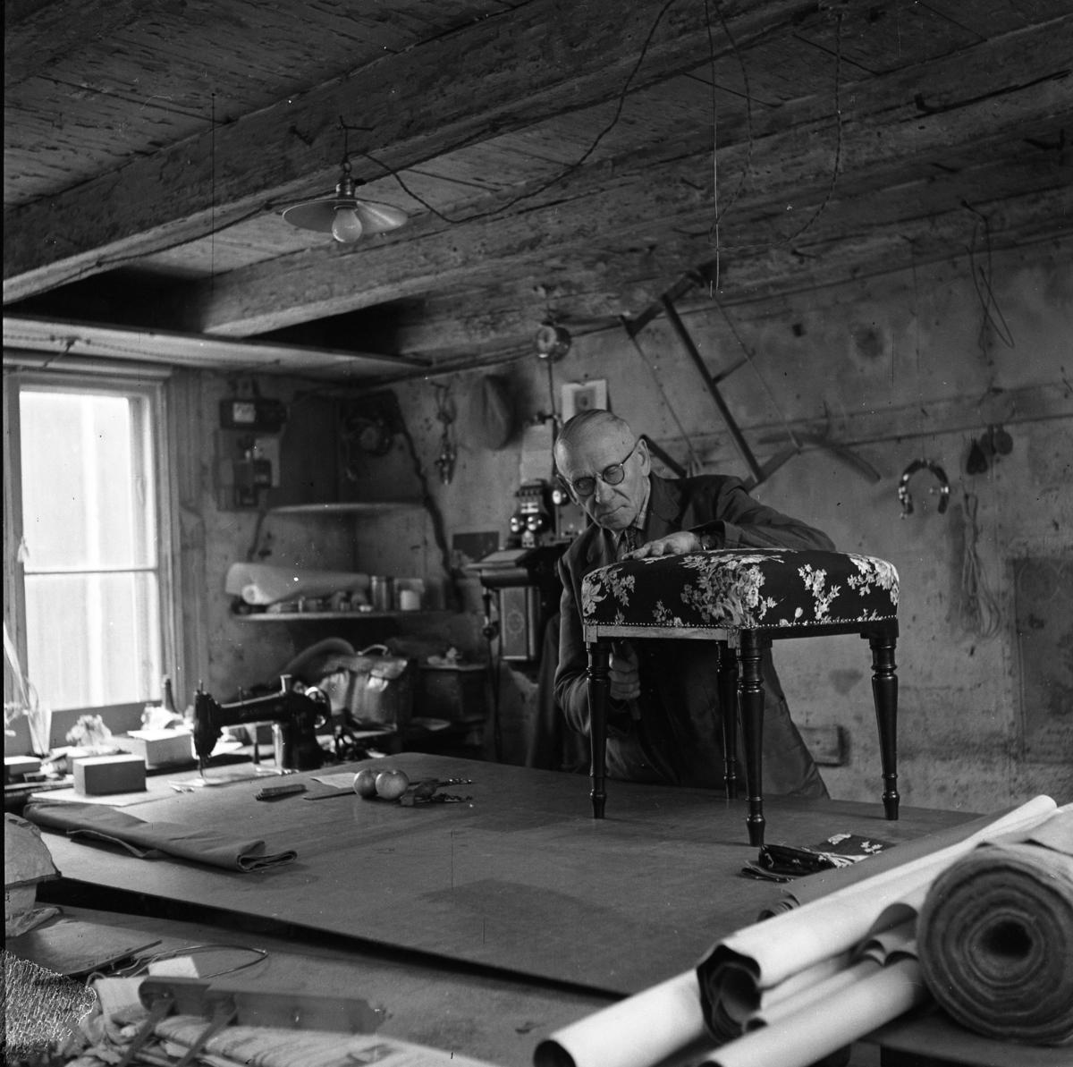 Tapetserare Fritz Lindkvist i sin verkstad i en dal av Fahlströmska gården vid Ahllöfsgatan. Fritz Lindqvist etablerade sig här 1907. Han arbetar med en tygklädd pall som står på ett stort arbetsbord. En symaskin syns till vänster. På väggen bakom honom hänger en såg och en telefon. I taket hänger en skomakarlampa.